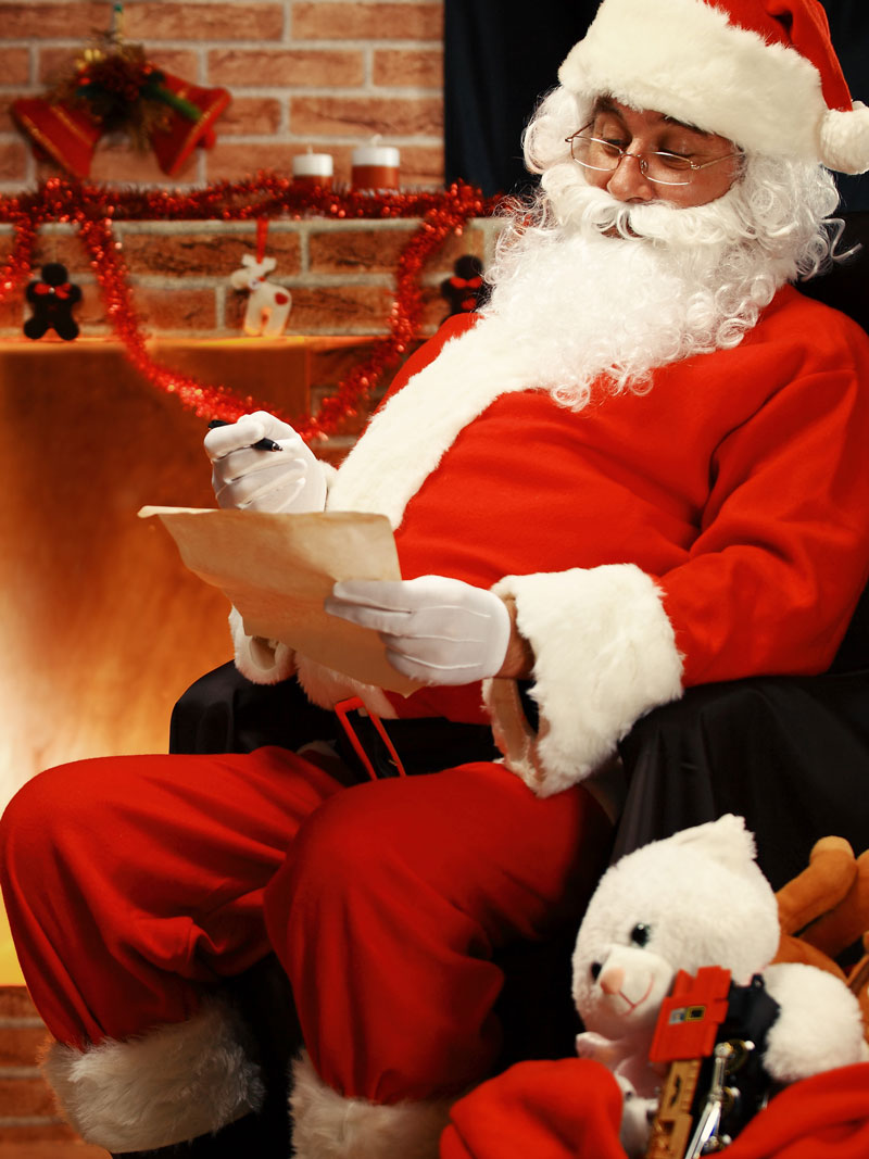 Santa in a chair reading Christmas lists